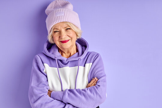 senior woman in purple pullover and hat posing, stylish woman enjoy being fashionable, looks at camera with crossed arms