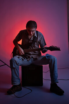 The guitarist play music with combo amplifier in beautiful red hall.