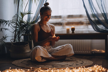 Obraz Young woman sitting on the floor, lights candles, enjoy meditation, do yoga exercise at home. Mental health, self care, No stress, healthy habit, mindfulness lifestyle, anxiety relief concept - fototapety do salonu