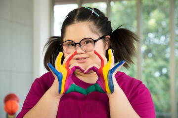 Portrait of Asian disabled child kid complex genetic disorders down syndrome girl with colorful painted hands