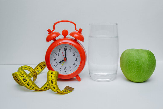 Red alarm clock with a glass of water and a green Apple close-up on a white background, the concept of diet and weight loss, Breakfast and a healthy lifestyle, slimness and preparation for summer