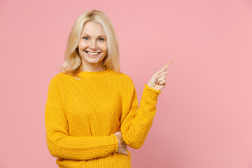 Smiling elderly gray-haired blonde woman lady 40s 50s years old in yellow casual sweater pointing index finger aside up on mock up copy space isolated on pastel pink color background studio portrait.
