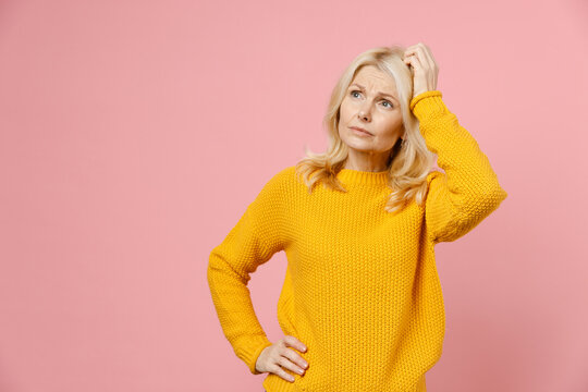 Worried pensive elderly gray-haired blonde woman lady 40s 50s years old wearing yellow casual sweater standing put hand on head looking aside isolated on pastel pink color background studio portrait.