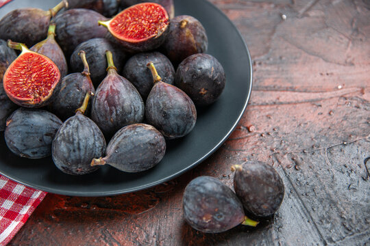 Side view of full fresh black mission figs split ones on a black plate on red stripped towel on colorful table half resolution photo