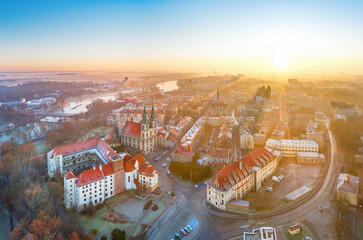 Fototapeta Brzeg, Poland. Aerial cityscape on sunrise with Piast castle and Church of the Holy Cross
