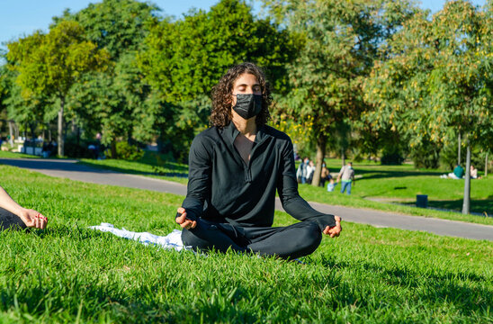 Young Attractive Man with Mask Meditating in a Yoga Class at the Park in Summer