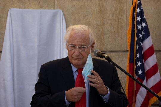 U.S. Ambassador to Israel David Friedman removes his mask before unveiling a plaque at the U.S. embassy in Jerusalem naming Kushner Courtyard after U.S. White House Senior Adviser Jared Kushner