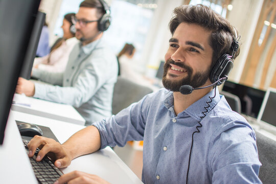 Young handsome technical support dispatcher working in call center.