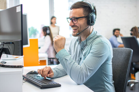Technical support operator working with headset in call center office