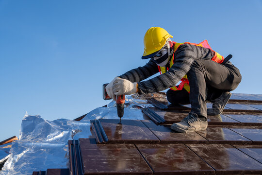 Construction worker install new ceramic tile roof with Roofing tools Electric drill used in the construction site.
