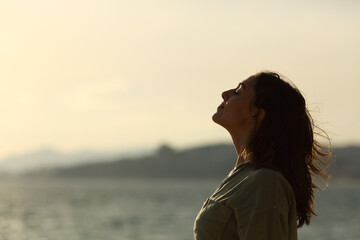 Back light of woman silhouette breathing fresh air on the beach