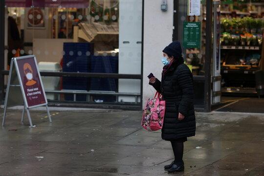 A woman waits for a bus outside a supermarket