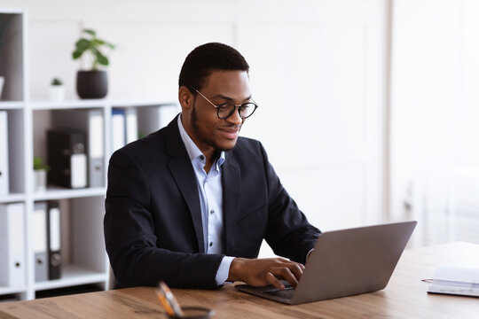 Cheerful black entrepreneur working with laptop, office interior