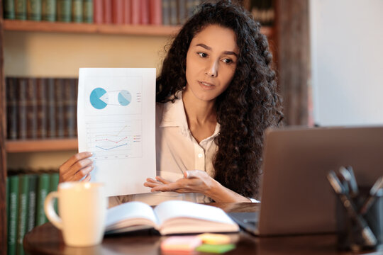 Woman sitting at desk, having videocall on laptop, holding paper