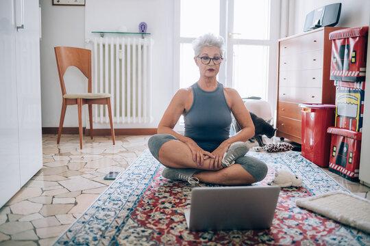 Woman sitting on floor, following online yoga class