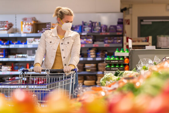 Teenage girl wearing protectice mask and gloves looking at vegetables at supermarket