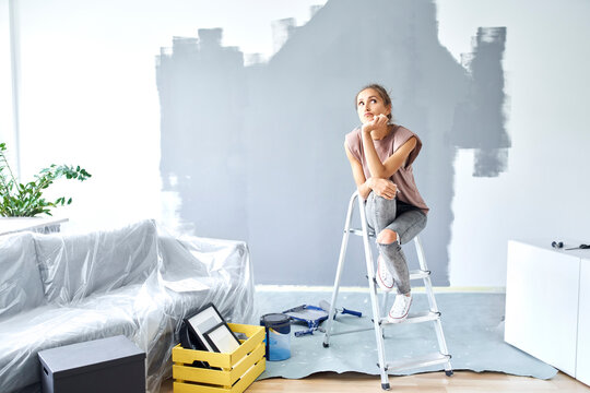 Thoughtful woman with head in hands sitting on ladder against wall at home