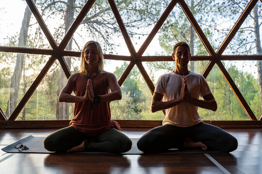 Male and female yoga instructors practicing lotus position against window in health retreat