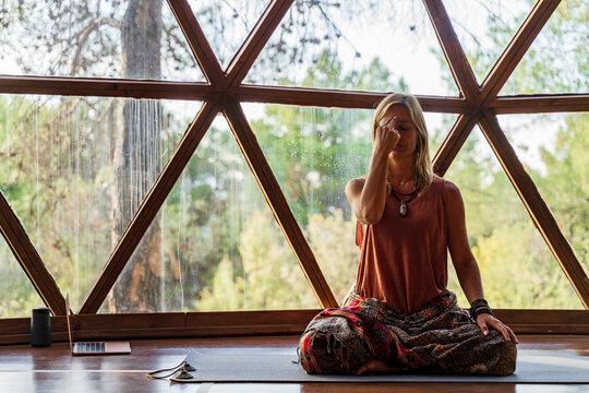 Mature female yoga instructor meditating against window at health spa
