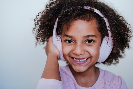 Girl listening music through headphones while standing against wall at home