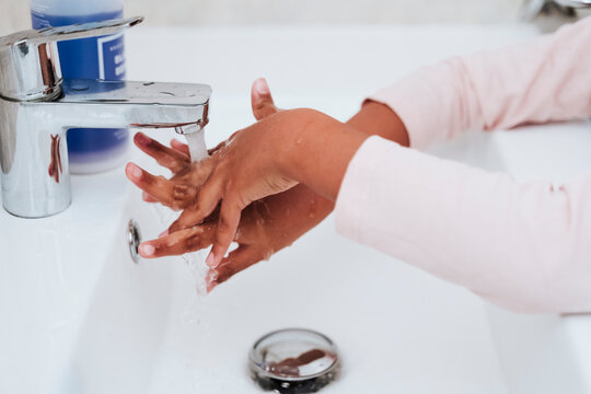 Cropped image of girl washing hands at home