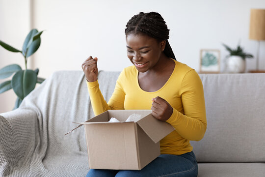 Happy black woman unboxing parcel at home, emotionally reacting to successful shopping