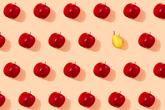 Pattern of single yellow pear surrounded by fresh red apples