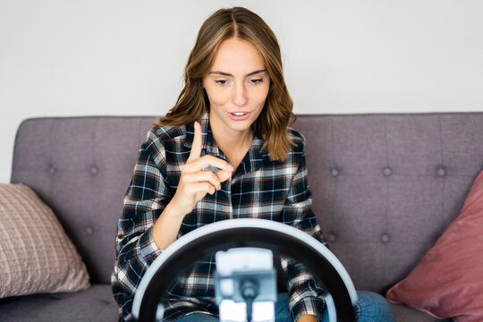 Young woman live streaming through mobile phone attached with ring light tripod while sitting on sofa at home