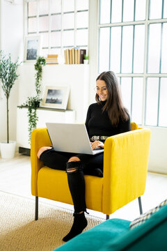 Smiling beautiful young woman using laptop for blogging while sitting on chair at home
