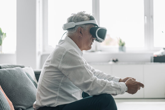 Businessman playing video game with virtual reality eyeglasses while sitting on sofa at office