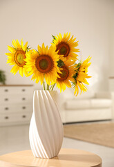 Bouquet of beautiful sunflowers in vase on table indoors