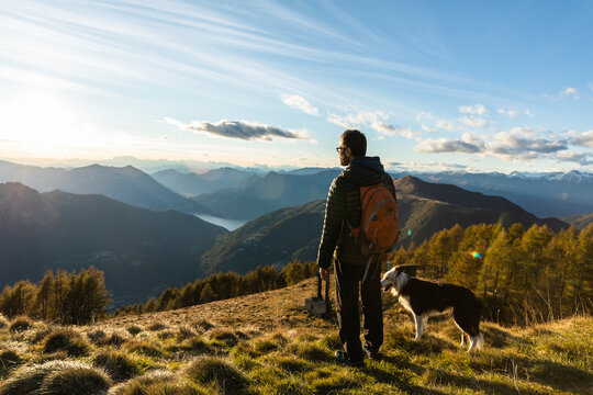 Hiker standing by dog while looking at mountain range during sunset