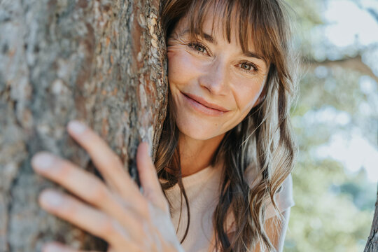 Smiling mature woman leaning on pine tree in public park