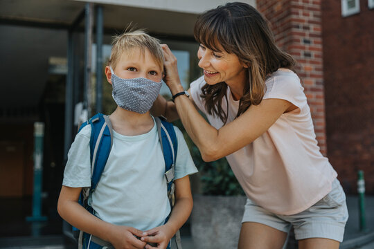 Mother helping son to wear protective face mask while going to school