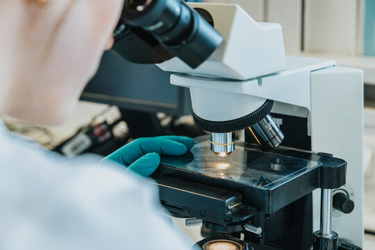 Young woman analyzing human brain microscope slide under microscope while sitting at laboratory