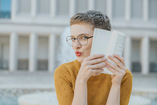 Mid adult woman hiding face with book while sitting on sunny day