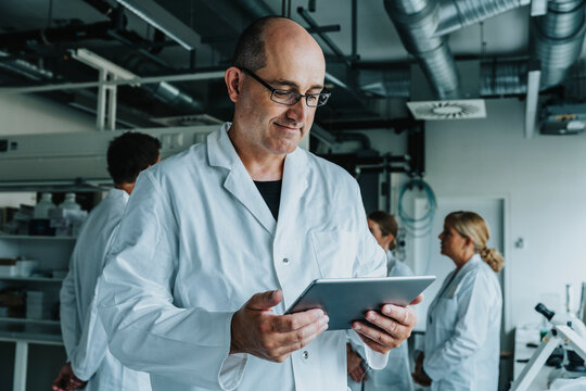 Scientist working on digital tablet while standing with coworker in background at laboratory