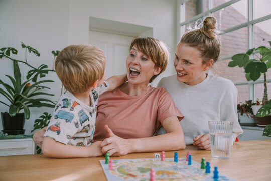 Cheerful mothers watching while son playing board game at home