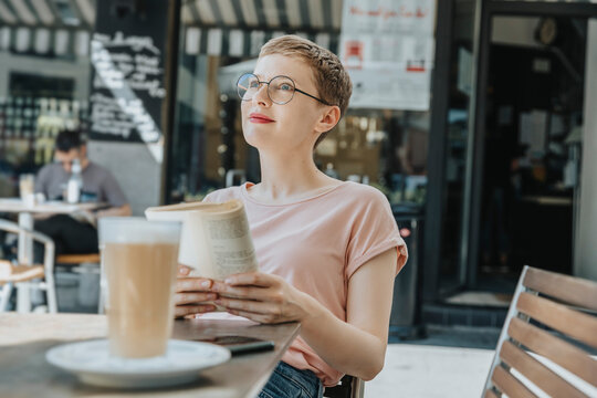 Mid adult woman looking away with book sitting in sidewalk cafe on sunny day