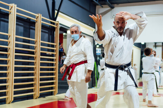 Instructor by male student practicing karate in class