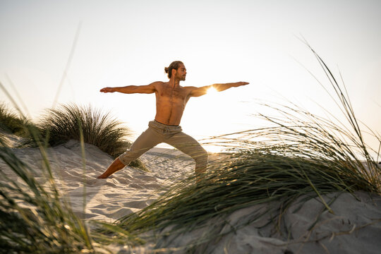 Shirtless young man practicing warrior 2 position yoga at beach against clear sky during sunset