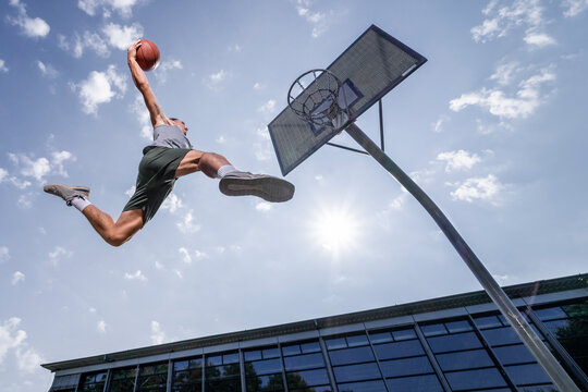 Young man dunking ball in hoop while playing basketball against sky on sunny day