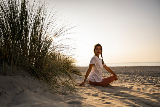 Beautiful young woman practicing yoga while sitting by plant at beach against clear sky during sunset