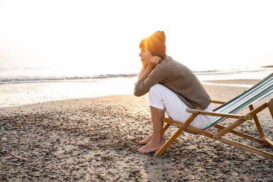 Back lit thoughtful young woman sitting on folding chair while looking away at beach against clear sky during sunset