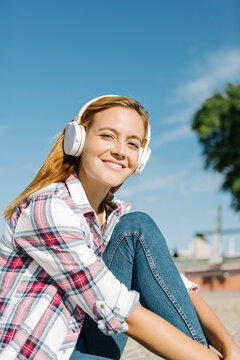 Smiling woman listening music on headphone sitting on footpath during sunny day