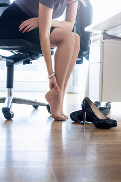 Female entrepreneur rubbing feet while sitting on chair in office