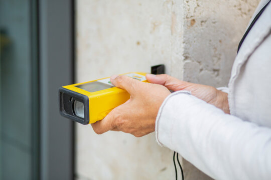 Female architect holding laser distance meter