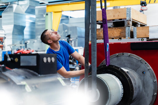 Male manual worker looking up while standing by machine at industry