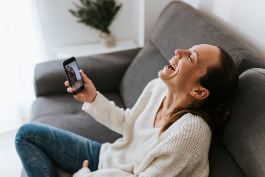 Woman laughing during video call with male friend in living room at home