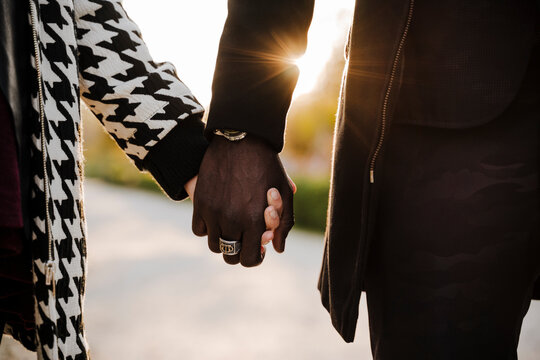 Multi ethnic couple holding hands in park during autumn